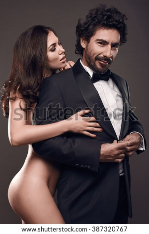 Fashionable portrait of elegant sexy couple in studio. Naked beautiful woman touching a brutal man in suit on on dark background - stock photo
