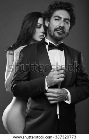 Fashionable portrait of elegant sexy couple in studio. Naked beautiful woman touching a brutal man in suit on dark background. Grayscale - stock photo