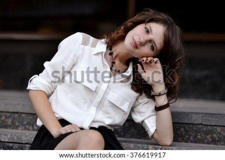 Fashionable portrait of fashionable,glamorous,beautiful,attractive,pretty,nice,gorgeous girl,student,school girl sitting on stairs near college,campus,library,university,school.Beautiful girl,study. - stock photo