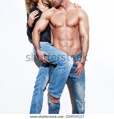 Fashionable sexy couple posing at white wall - stock photo