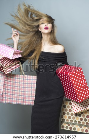 Fashionable shopping girl with streamed hair in the breeze in black dress holding colorful packages and box, vertical picture - stock photo