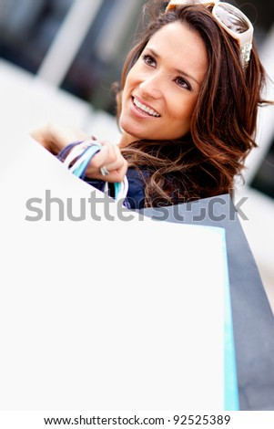 Fashionable shopping woman holding bags and smiling - stock photo