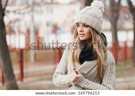 fashionable stylish girl in white beanie and knit jacket. Outdoors, lifestyle - stock photo