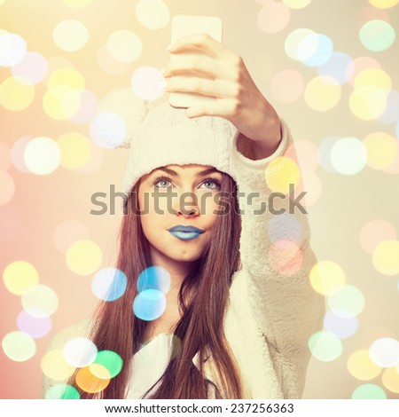 Fashionable teenage girl with blue lipstick taking a selfie. Cute young woman wearing beanie and makeup taking a self portrait with smart phone. Square format, instagram filter, string light bokeh. - stock photo