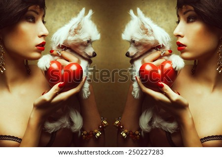 Fashionable Valentines Day concept. Profile portrait of model with red lips holding red heart (love symbol) and white little chinese crested dog, posing over golden background. Close up. Studio shot - stock photo