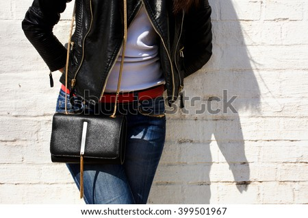 Fashionable woman in a black leather jacket and jeans with a black clutch , accessories , white background, hands behind his back , Stylish accessories - stock photo