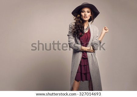 Fashionable woman in a hat, dress and long grey sweater, accessories, high heels, posing in studio. Fashion autumn photo - stock photo