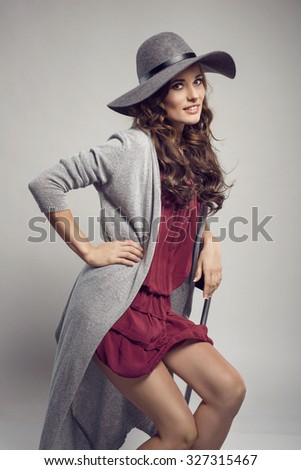 Fashionable woman in a hat, dress and long grey sweater, posing in studio. Fashion autumn photo. Wonderful hair style - stock photo