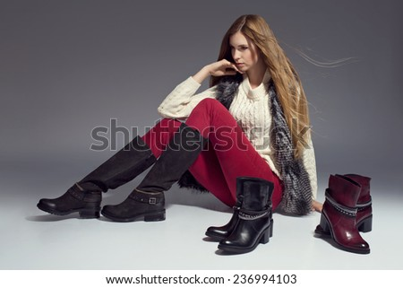 Fashionable woman in boots and autumn clothes, posing in studio - stock photo