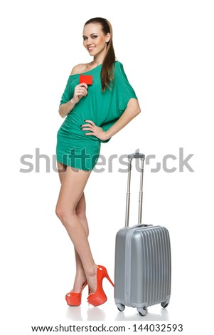 Fashionable woman in full length wearing green mini dress standing with travel bag and showing blank credit card, against white background - stock photo