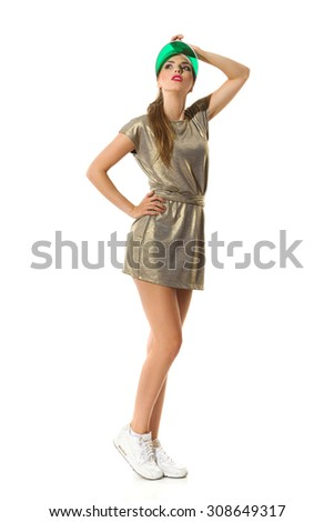 Fashionable Woman In Gold Mini Dress. Confident young woman in gold mini dress, white sneakers and green sun visor cap posing with hand on head. Full length studio shot isolated on white. - stock photo