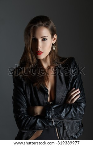 Fashionable woman in leather jacket on grey background - stock photo