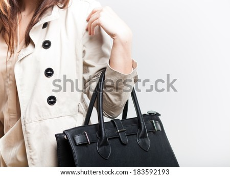 Fashionable woman in white coat with black leather bag - stock photo