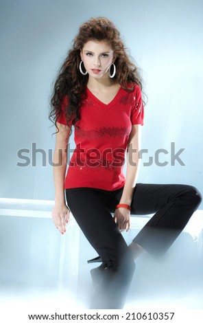 fashionable woman posing near the cube on light background - stock photo