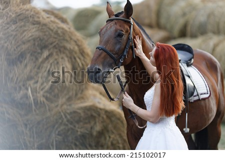Fashionable woman riding a horse in sunny day. Long curly hair. Fashion colors.  - stock photo