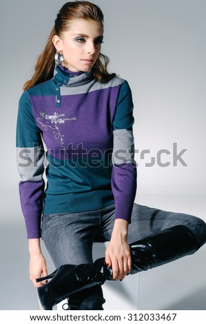 fashionable woman sitting cube in light background - stock photo