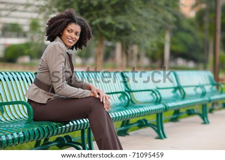 Fashionable woman sitting in the park - stock photo
