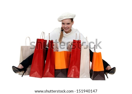Fashionable woman surrounded by her shopping bags - stock photo