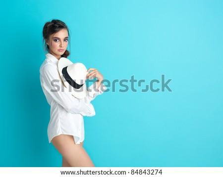 fashionable woman white shirt hat blue background - stock photo