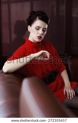 fashionable woman with emotion sitting on the couch interior - stock photo