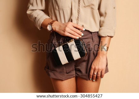 Fashionable woman with  stylish black and white clutch , accessories, watch . Elegant outfit silk blouse and  brown shorts - stock photo