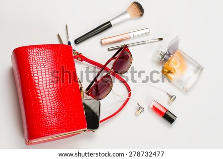 Fashionable women's handbag. Open red ladies handbag with scattered accessories. - stock photo