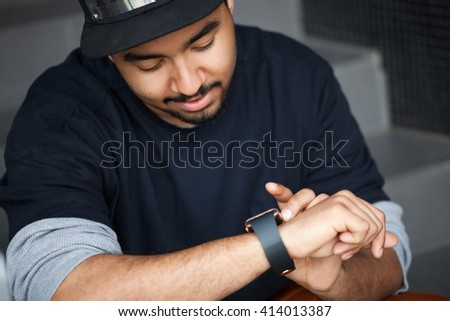 Fashionable young African American boy using his trendy smart watch.Modern gadget that lets you always stay connected to internet,social media from everywhere - stock photo