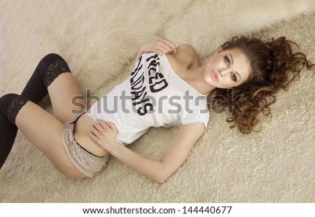 Fashionable young brunette sensual woman lying on fur, looking at camera. - stock photo