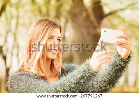Fashionable young Caucasian blonde woman smiling taking a selfie using smart phone outdoors in park on sunny spring day. Closeup, blurred background, retouched, horizontal. - stock photo