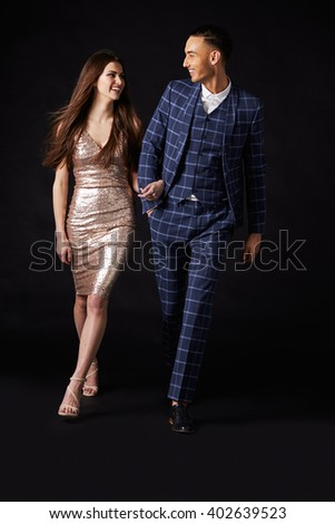 Fashionable young couple walking together arm in arm - stock photo