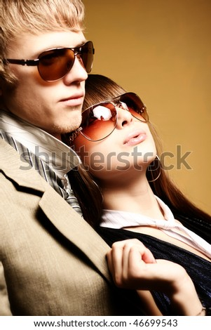 Fashionable young couple wearing sunglasses - stock photo