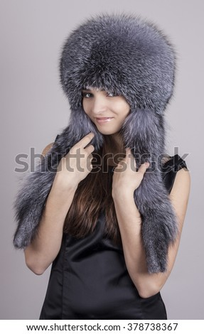 Fashionable young girl in a hat. Hat fur fox. - stock photo