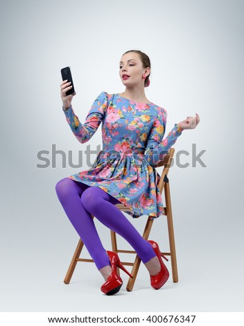 Fashionable young girl in dress sitting on chair making selfie - stock photo