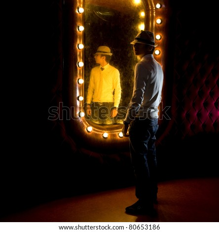 fashionable young man looks at himself in mirror - stock photo