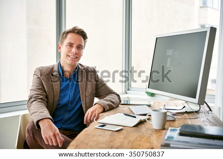 Fashionable young man sitting at his desk in a light and bright office space with windows, looking positive and confident - stock photo