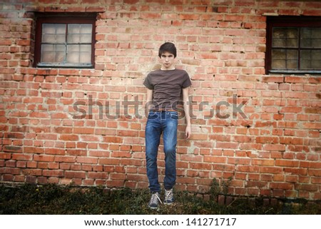 fashionable young man standing next to a wall outdoors - stock photo