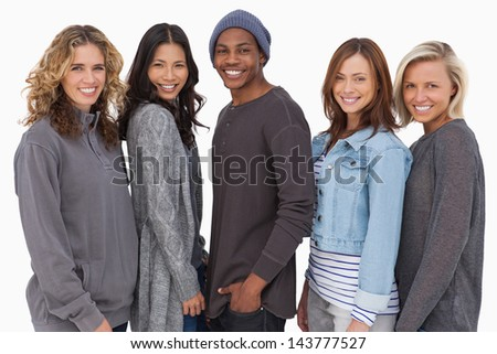 Fashionable young people in a row smiling on white background - stock photo