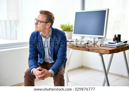 Fashionable young professional sitting in his neat and modern office looking away thoughtfully out of the window - stock photo
