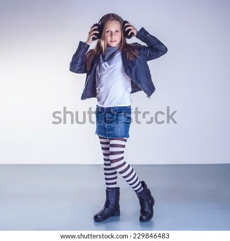 Fashionable young teenager girl posing in studio, looking at camera. - stock photo