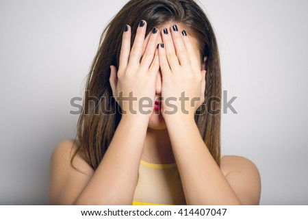 Fashionable young woman covers her face with her hands, in yellow close-up isolated - stock photo