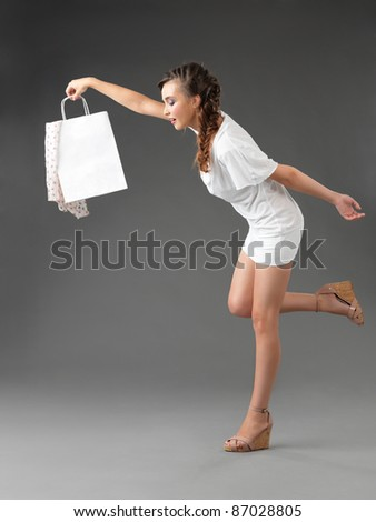 fashionable young woman holding a shoppping bag, tumbling - stock photo