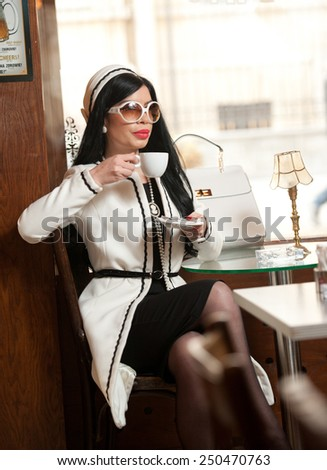 Fashionable young woman in black and white outfit drinking coffee in restaurant. Beautiful brunette in elegant scenery holding a cup of coffee. Attractive lady with sunglasses and coat in coffee shop - stock photo