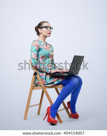 Fashionable young woman in dress and glasses sitting on chair with a laptop - stock photo