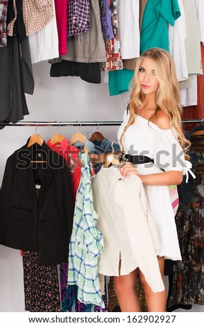 Fashionable young woman shopping in a clothing store. - stock photo