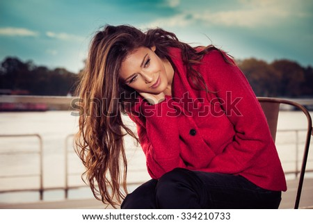 fashionable young woman sit at outdoor cafe by the river  wearing red coat, autumn day - stock photo