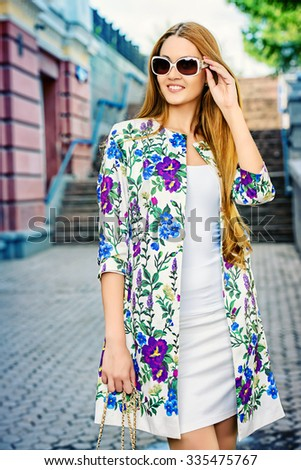 Fashionable young woman walking on a city street and smiling.  - stock photo