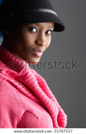Fashionable Young Woman Wearing Cap And Knitwear In Studio - stock photo