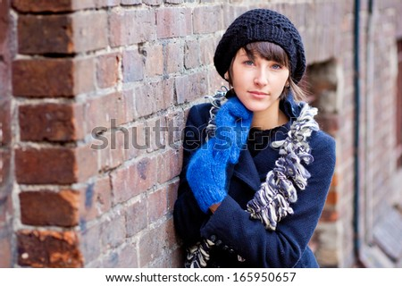 fashionable young woman wearing dark blue beret and blue gloves - stock photo