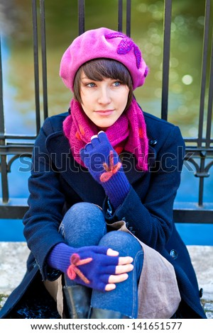 fashionable young woman wearing pink beret, scarf and blue gloves - stock photo