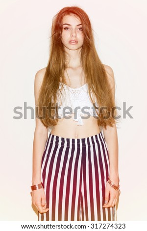 Fashionable young woman with long messy hair in summer outfit. Teenage girl with messy bun wearing white crochet crop top and striped pants posing. Pastel filter applied, medium retouch, vertical - stock photo